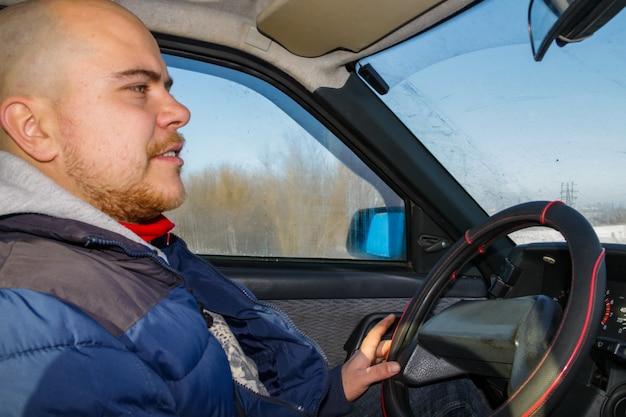 冬の道で車を運転している若い男。内面図