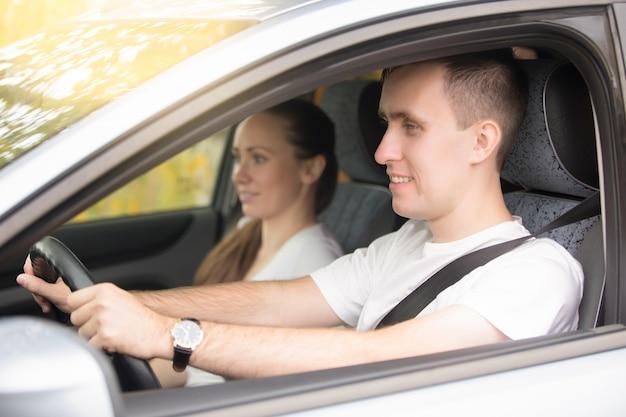젊은 남자 운전 및 여자 차 근처에 앉아