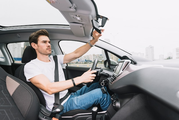 Young man driving car adjusting rear view mirror