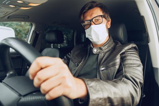 의료 마스크에 차를 운전하는 젊은 남자