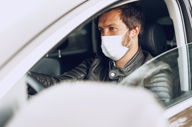 Young man driving car in medical mask