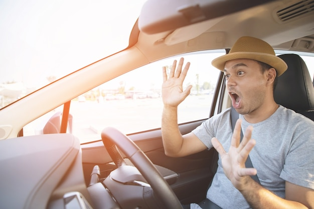 Young man driving a car shocked about to have traffic accident