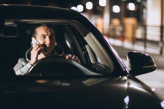 若い男が夜に彼の車を運転し、電話で話しています。