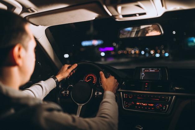 Молодой человек за рулем своего автомобиля в ночное время