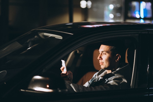 Young man driving his car at a night time and talking on the phone