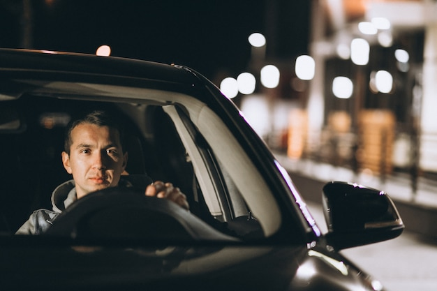 Young man driving his car at a night time