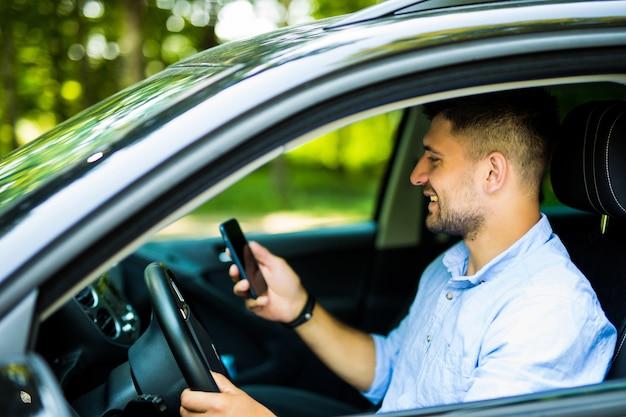 若い男が携帯電話を使用して彼の車で運転