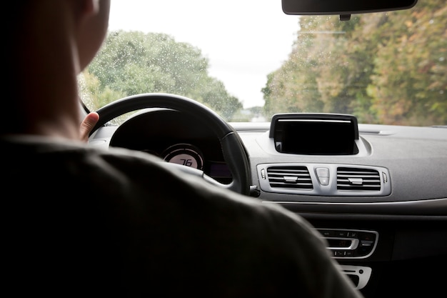 Young man driving the modern car on asphalt road