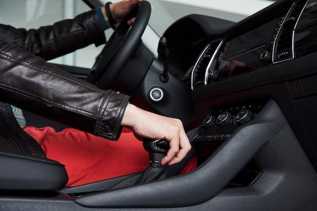 Молодой человек за рулем нового автомобиля в салоне