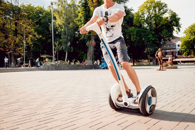 若い男が公園でセグウェイを運転