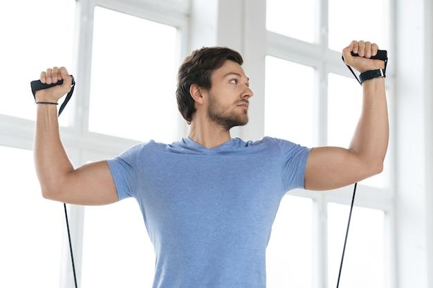Молодой человек во время тренировки с резинками сопротивления в тренажерном зале. упражнение на жим от плеч стоя.