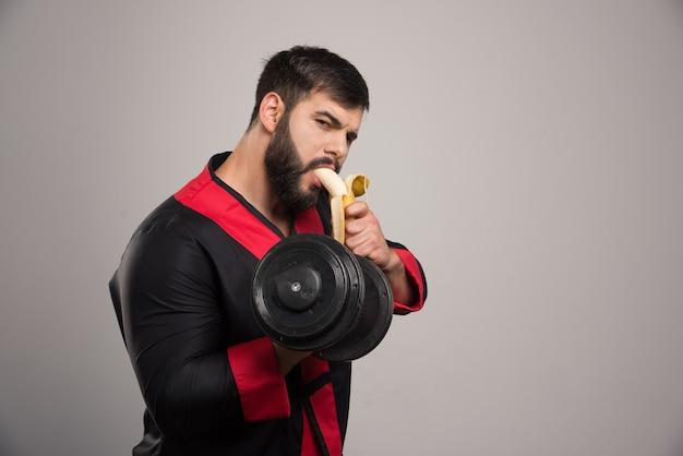 Молодой человек ест банан и держит гантель.