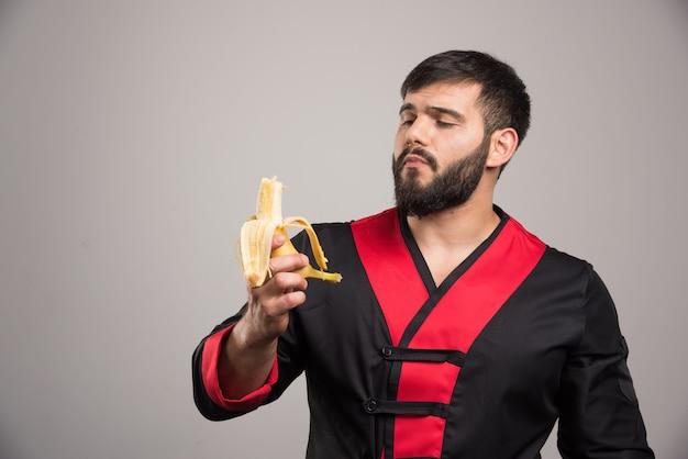 灰色の壁にバナナを食べる若い男。