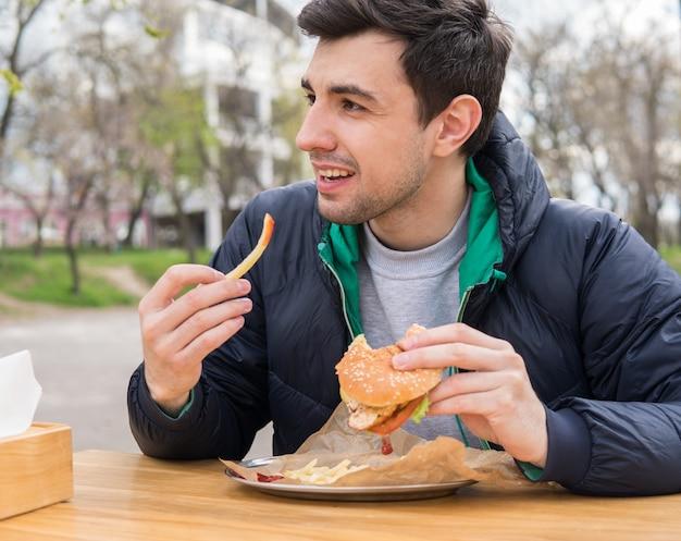屋台のカフェでフライドポテトとハンバーガーを食べる若い男。ファーストフードを食べる