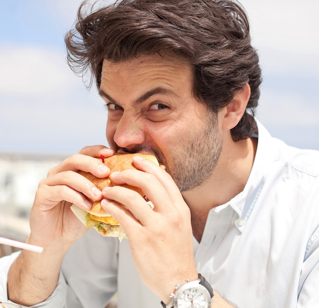 ハンバーガーを食べる若い男