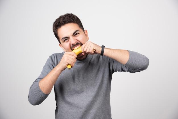 Un giovane uomo che mangia una banana su un muro bianco.