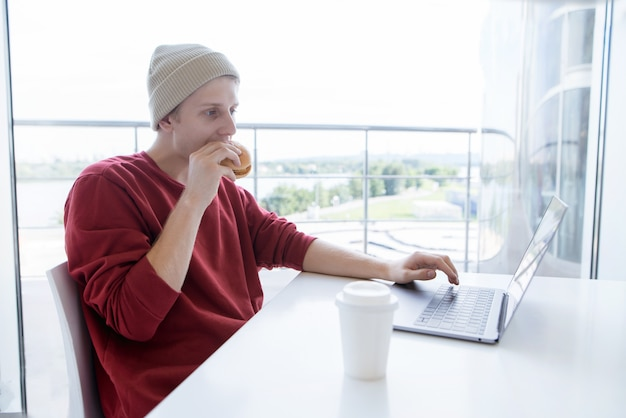 Young man eating a burger and working on a laptop