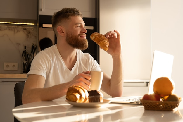 Young man eating croissant and drinking tea or coffee on breakfast. smiling european bearded guy sitting at table with food and laptop. interior of kitchen in modern apartment. sunny morning time