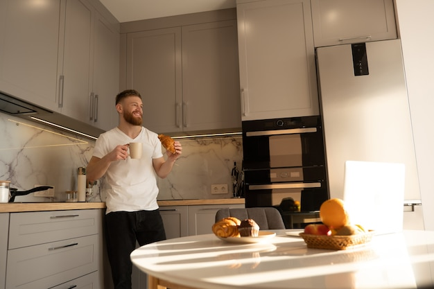 Young man eating croissant and drinking tea or coffee on breakfast. smiling european bearded guy standing near table with food and laptop. interior of kitchen in modern apartment. sunny morning time