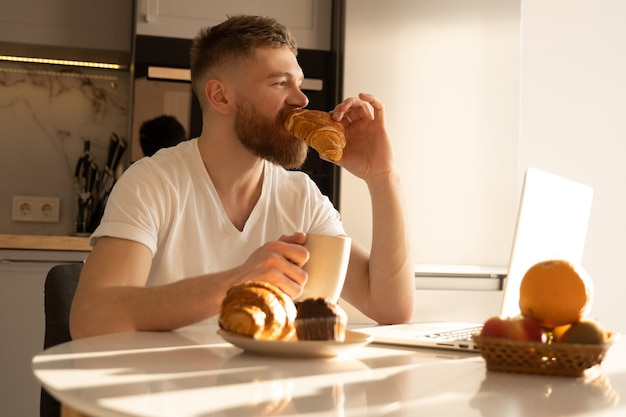 Young man eating croissant and drinking tea or coffee on breakfast. thoughtful european bearded guy sitting at table with food and laptop. interior of kitchen in modern apartment. sunny morning time