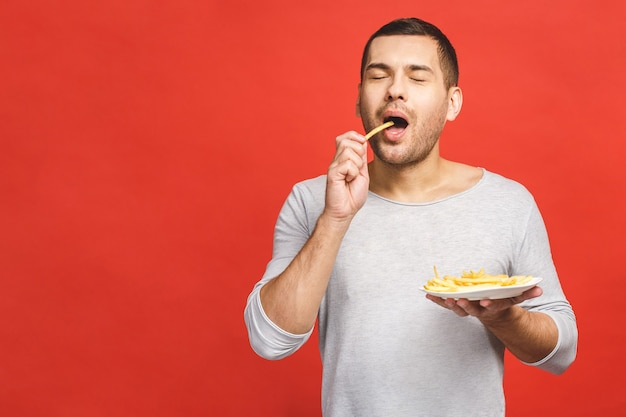 Young man eating french fries