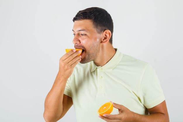 Tシャツのフロントビューでオレンジスライスの1つを食べる若い男。