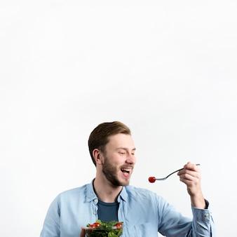 Молодой человек ест красные помидоры черри и салат на белом фоне
