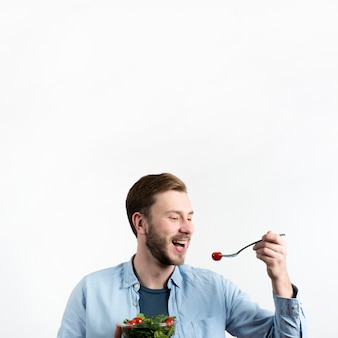 Young man eating red cherry tomato and salad in white background