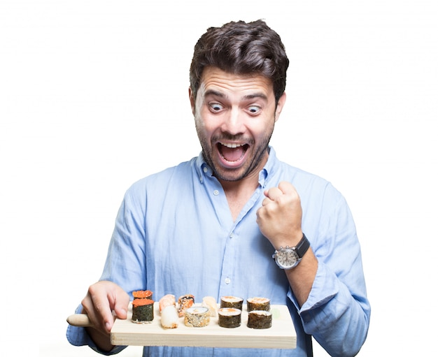 Young man eating sushi on white background