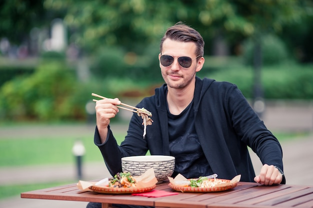 Young man eating take away noodles on the street