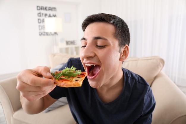 家でおいしいピザを食べる若い男