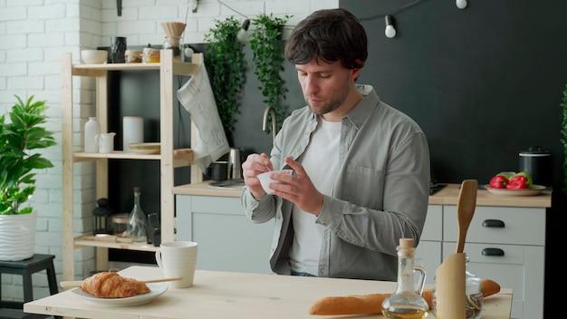 Молодой человек ест йогурт на кухне дома