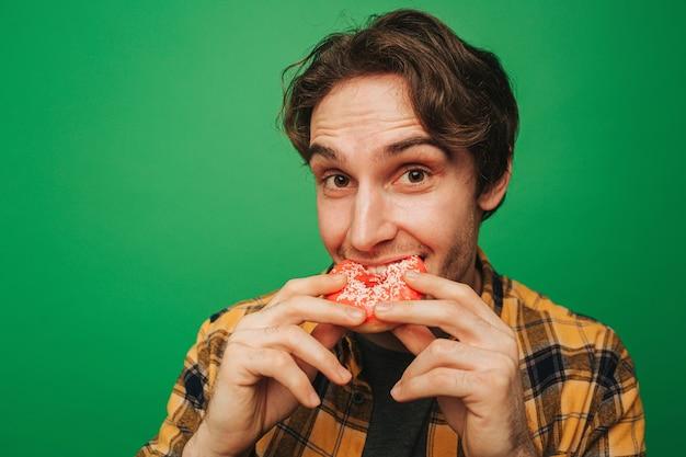 젊은 남자가 기쁨으로 도넛을 먹는다.
