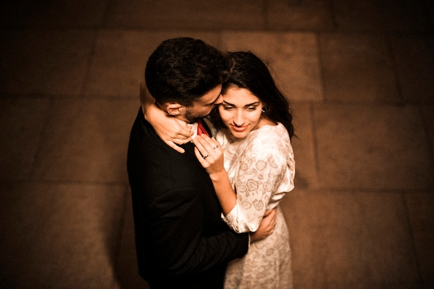 Young man embracing charming woman
