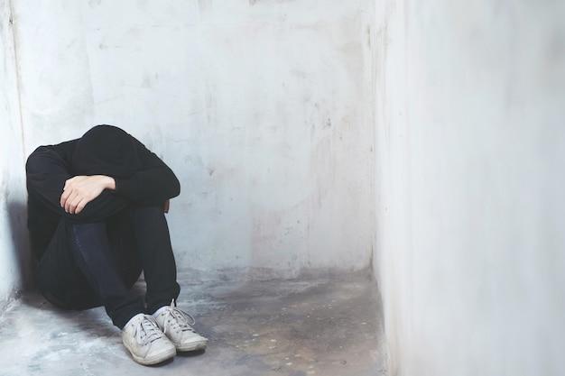 젊은 남자 감정 긴장 미안 슬픈. 우울한 남자는 마음이 없어서 바닥에 머리를 숙여 앉으십시오. 극적인 개념