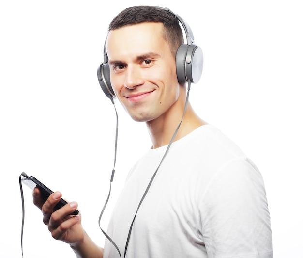 彼のヘッドフォンで音楽を楽しんでいる若い男