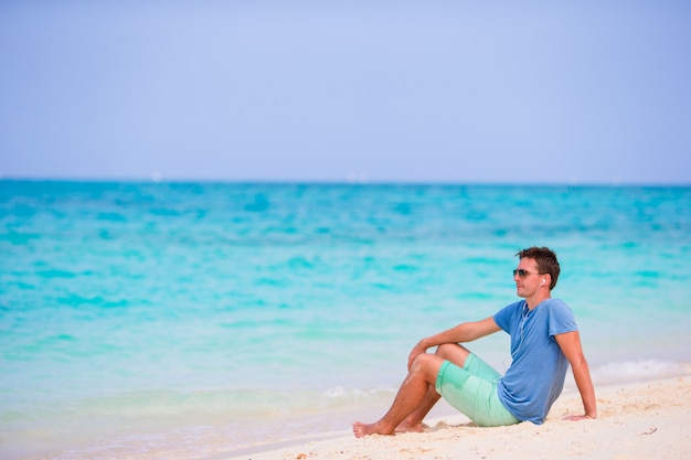 Young man enjoying the music on white sandy beach. happy tourist relaxing on summer tropical vacation.