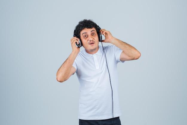 흰색 티셔츠에 헤드폰을 끼고 음악을 즐기고 행복해 보이는 젊은 남자.