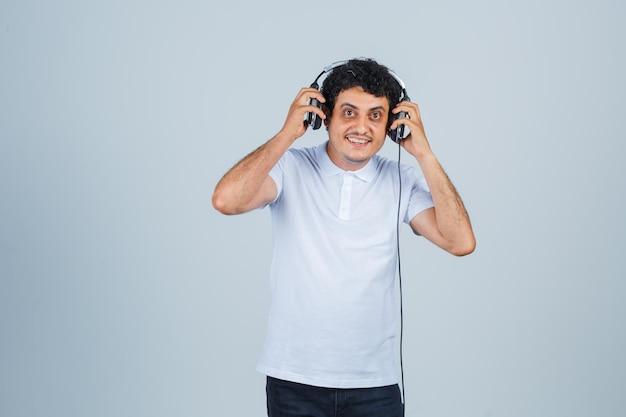 흰색 티셔츠에 헤드폰을 끼고 음악을 즐기고 앞모습을 바라보는 명랑한 청년.
