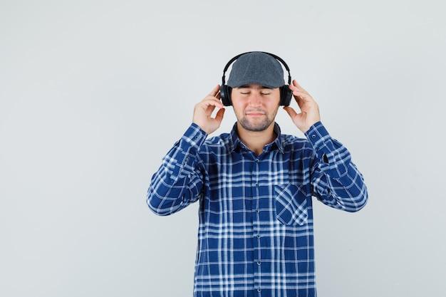 Giovane che gode della musica con le cuffie in camicia, berretto e che sembra pacifico. vista frontale.