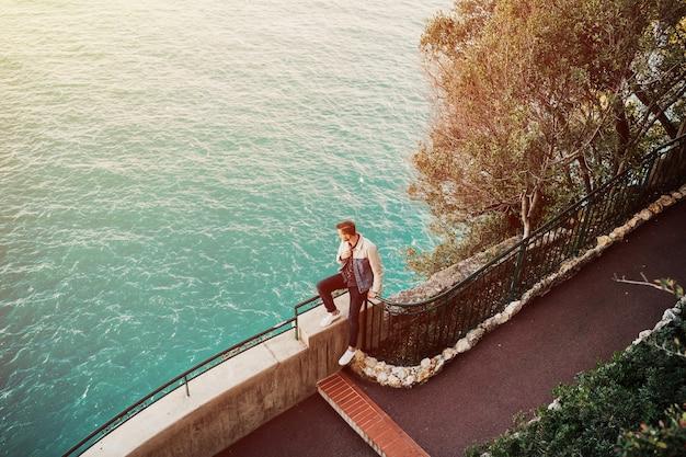 モナコの海の上のフレンチリビエラのモンテカルロの王子の宮殿からパノラマの景色を楽しむ若い男