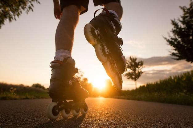Молодой человек наслаждается катанием на роликах по велосипедной дорожке во время прекрасного летнего заката