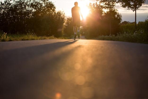 素敵な夏の日没時に自転車道でローラースケートを楽しんでいる若い男