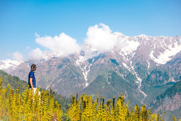 Молодой человек, наслаждаясь прекрасным видом на горы