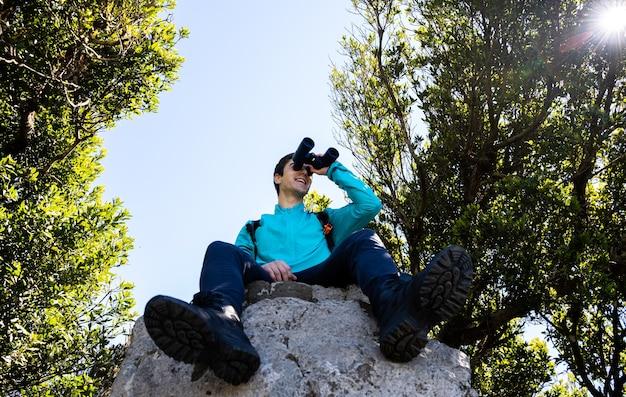 산 꼭대기에서 쌍안경으로 경치를 즐기는 청년