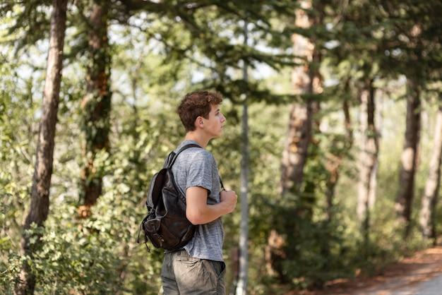 森の中を散歩を楽しんでいる若い男