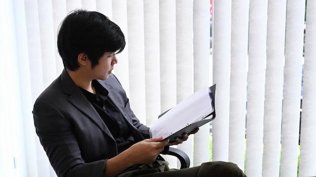 Молодой человек-предприниматель, проверка финансовых отчетов в современном офисе.