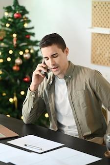 Молодой человек-предприниматель в домашнем офисе и разговаривает по мобильному телефону.