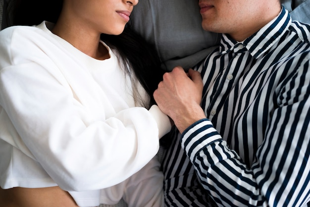 Young man and ethnic woman lying on bed and holding hands