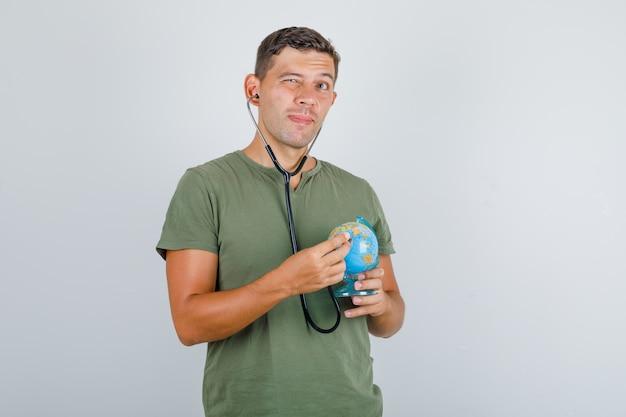 Молодой человек изучает глобус со стетоскопом в зеленой футболке армии, вид спереди.